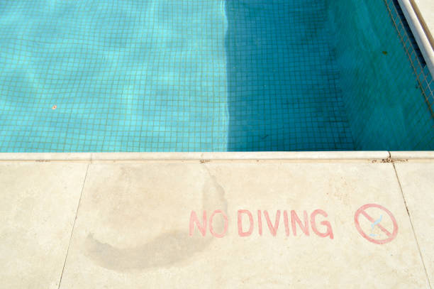Red paint inscription no diving for safety on the background of the pool on a tropical warm sea resort and copy space Red paint inscription no diving for safety on the background of the pool on a tropical warm sea resort and copy space. shallow stock pictures, royalty-free photos & images