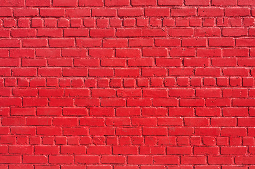 Close-up texture background image of a red painted brick wall.