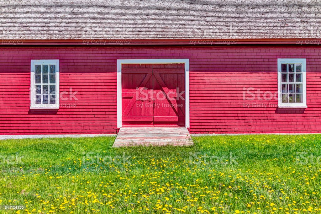 Red painted bright vintage shed with yellow dandelion flowers in summer landscape field in countryside stock photo