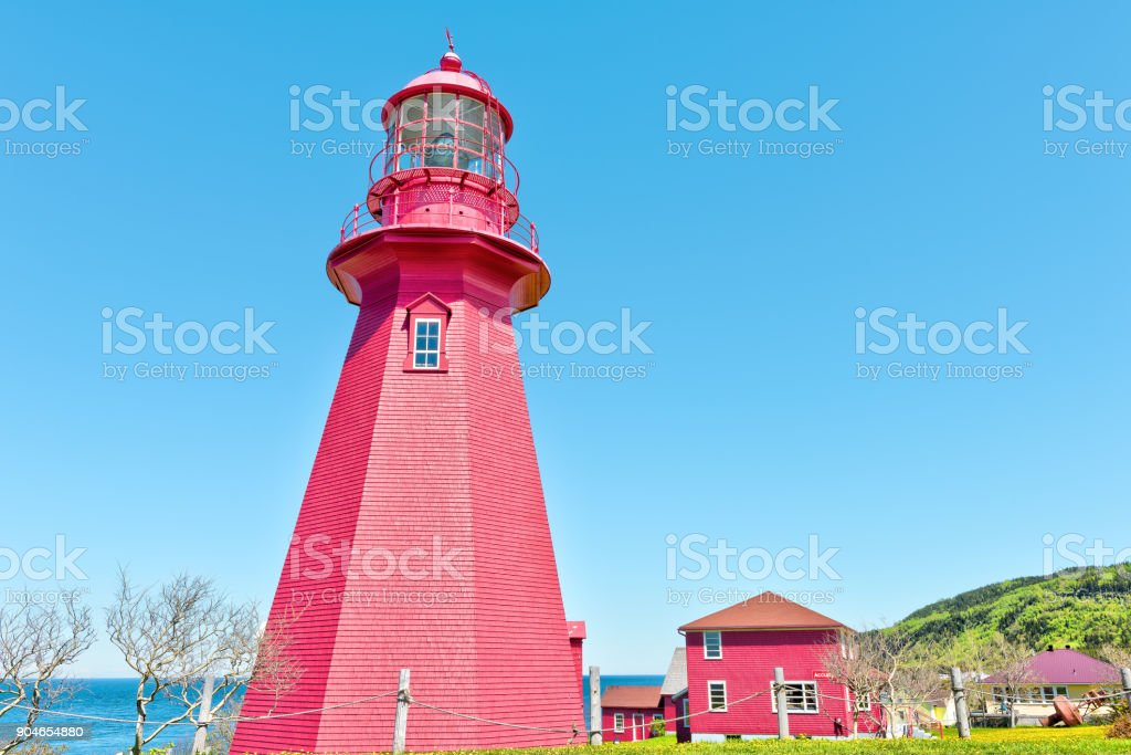 Red painted lighthouse with yellow dandelion flowers in La Martre in the Gaspe Peninsula, Quebec, Canada, Gaspesie region stock photo