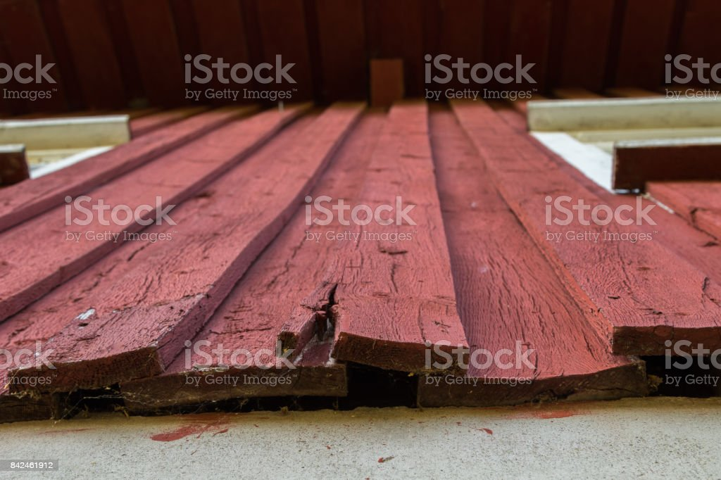 A red painted wood facade on a house which is rotten in the bottom needing replacement repair. stock photo