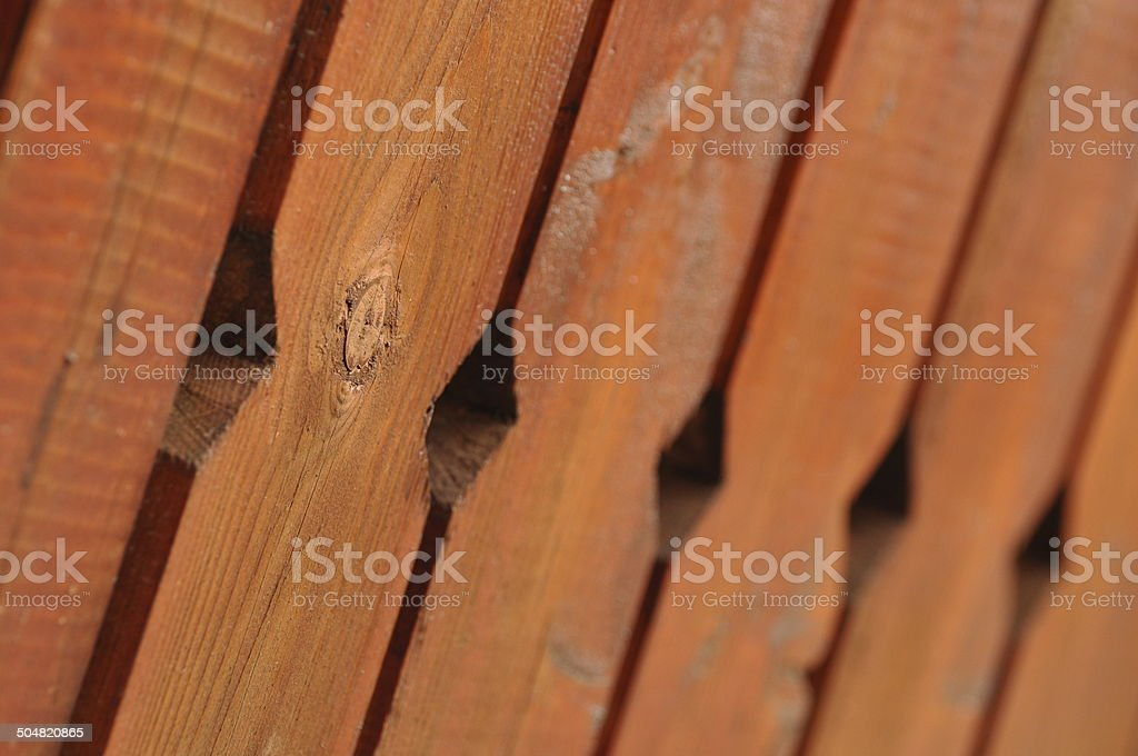 Red painted wooden planks fence with holes royalty-free stock photo