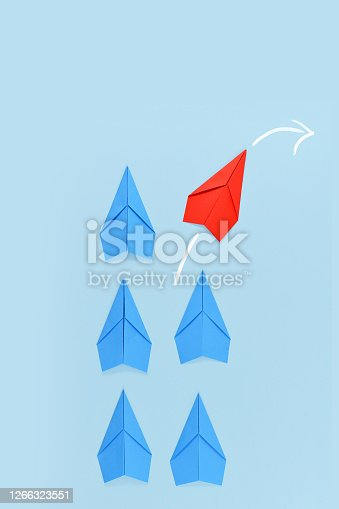 Red paper airplane changing course while leading blue airplanes. Concept for leadership, discovery and new ideas on blue background