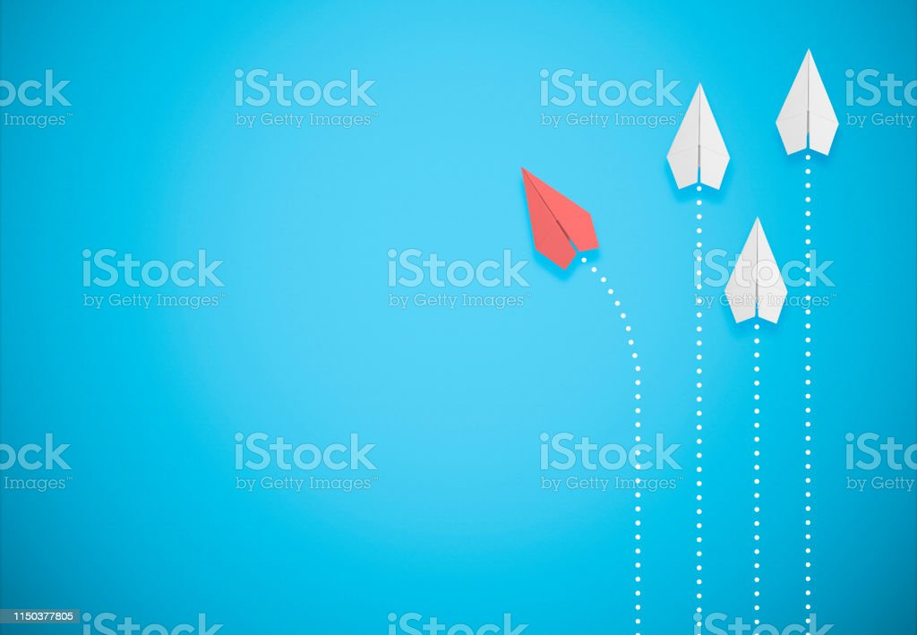 red paper airplane on blue background goes different direction red paper airplane on blue background goes different direction Abstract Stock Photo