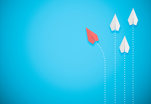 Red Paper Airplane On Blue Background Goes Different Direction Stock Photo - Download Image Now