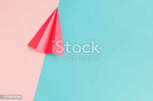 istock Red paper airplane on pastel pink and blue background. 1019858066