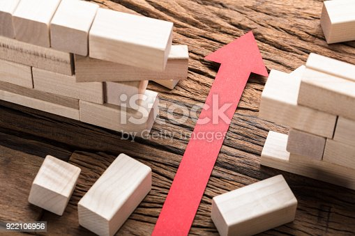istock Red Paper Arrow Amidst Blocks On Wooden Table 922106956