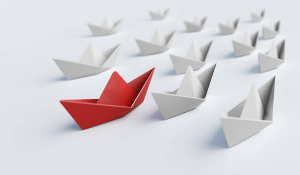 Red paper boat in front of others. Leadership and difference concept. 3D rendered illustration. stock photo