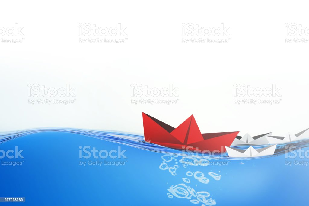 Red paper boats sailing in the sea, leadership concept.