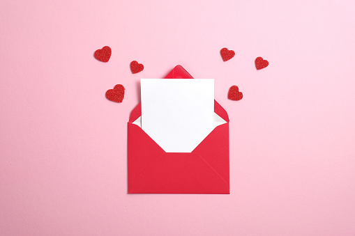 Red paper envelope with blank white note mockup inside and Valentines hearts on pink background. Flat lay, top view. Romantic love letter for Valentine's day concept.