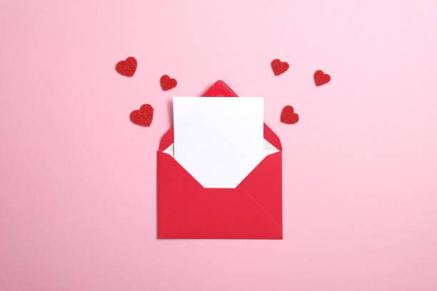 koperta z czerwonego papieru z pustą białą nutą w środku i walentynkowe serca na różowym tle. płaski lay, widok z góry. romantyczny list miłosny do koncepcji walentynki. - kartka na walentynki zdjęcia i obrazy z banku zdjęć