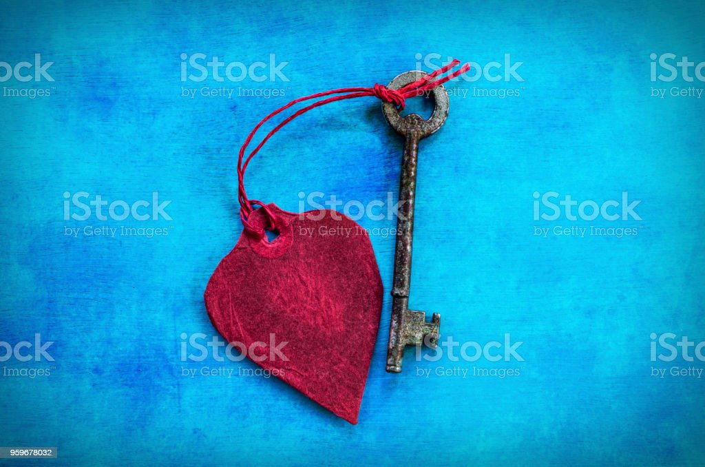 Red Paper Heart & A Key in the Centre of a Blue Background stock photo