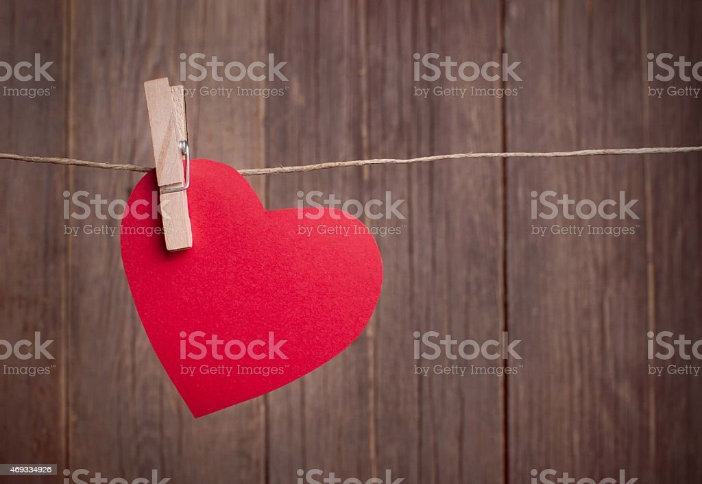 Red paper heart hanging on the clothesline stock photo