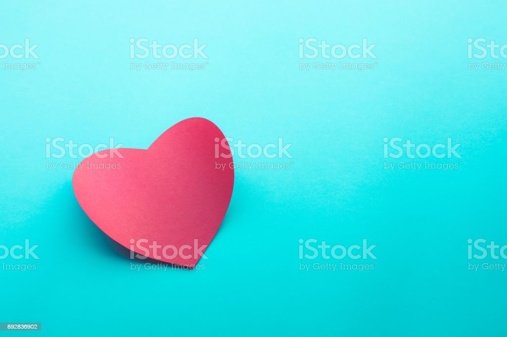Red paper heart shape on blue background.love, valentine,wedding concepts stock photo