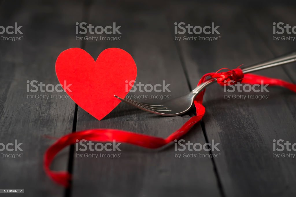 Red paper hearts and a fork with a ribbon. Dark wooden background. Copy space. St. Valentine's Day. stock photo