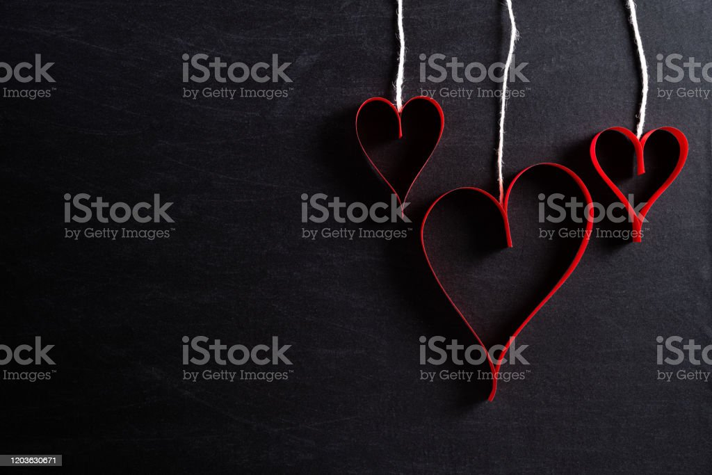 Red paper hearts hanging on ropes on black background. Love and Valentine's day concept. Red paper hearts hanging on ropes on black background. Love and Valentine's day concept. Abstract Stock Photo