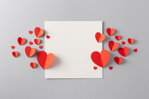 Red paper hearts with blank white note for Valentine's Day message.
