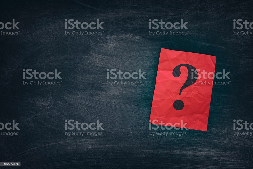 Red paper note with question marks on black board stock photo