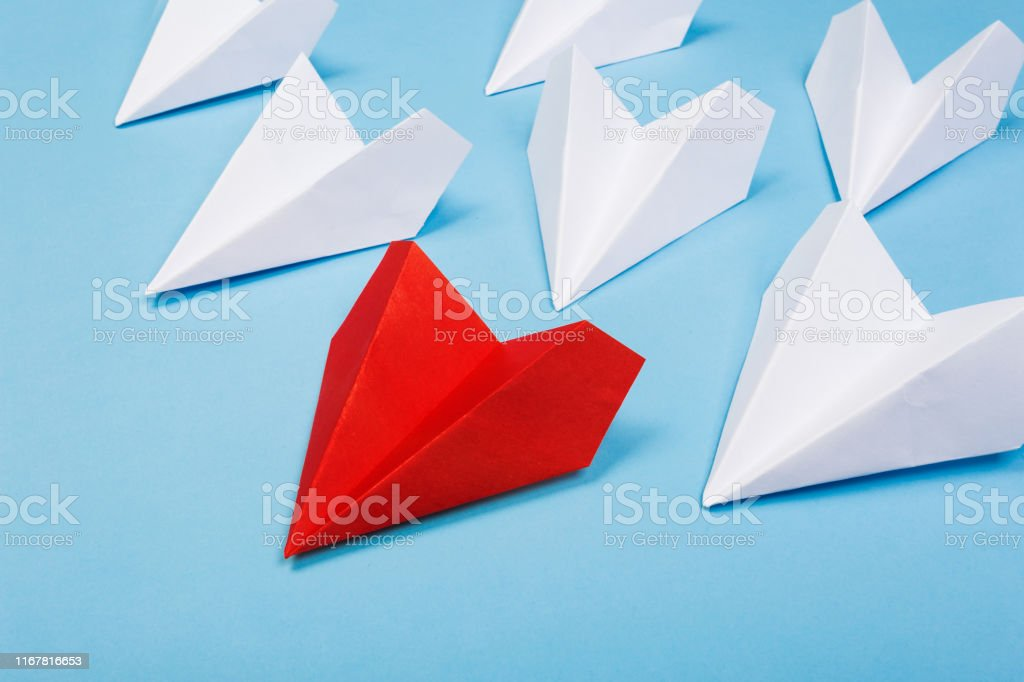 Red paper plane are different from others on blue background. Think...