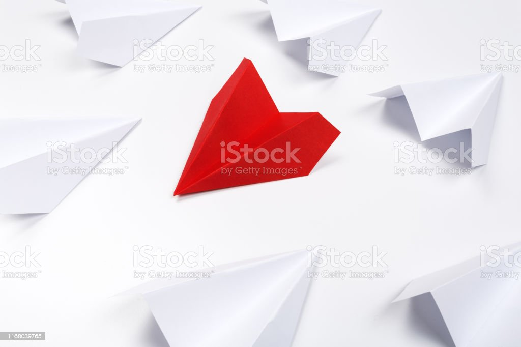 Red paper plane are different from others on white background. Think...