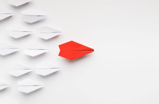 Red paper plane leading another ones, leadership concept Opinion leadership concept. Red paper plane leading another ones, influencing the crowd, white background, top view with free space persuasion stock pictures, royalty-free photos & images