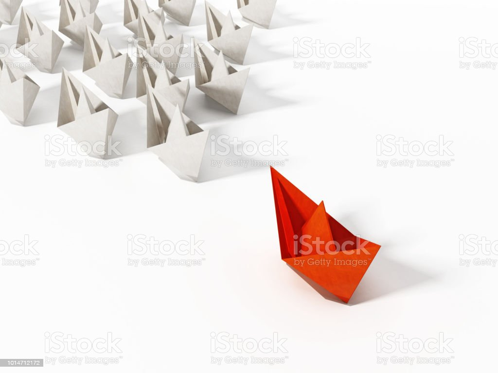 Red paper ship leading large group of white ships.