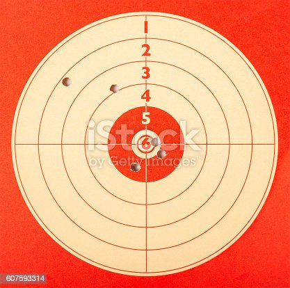 A practice target in red paper has received five bullet holes during a shooting session.