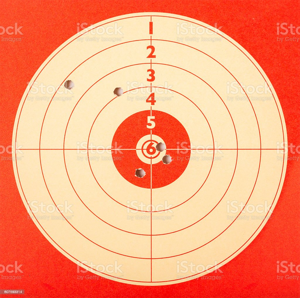 Red paper target shot with bullet holes stock photo