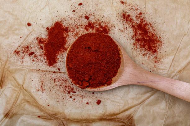 rode paprika in houten lepel (specerijen collectie). op rustieke achtergrond. - paprikapoeder stockfoto's en -beelden