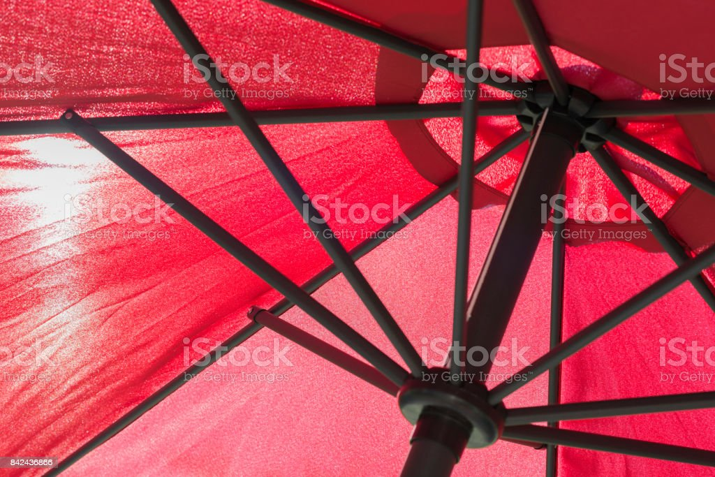 Red parasol with the sun translucent by the canvas stock photo
