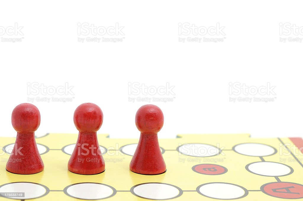 Red parcheesi board game pieces on white background stock photo