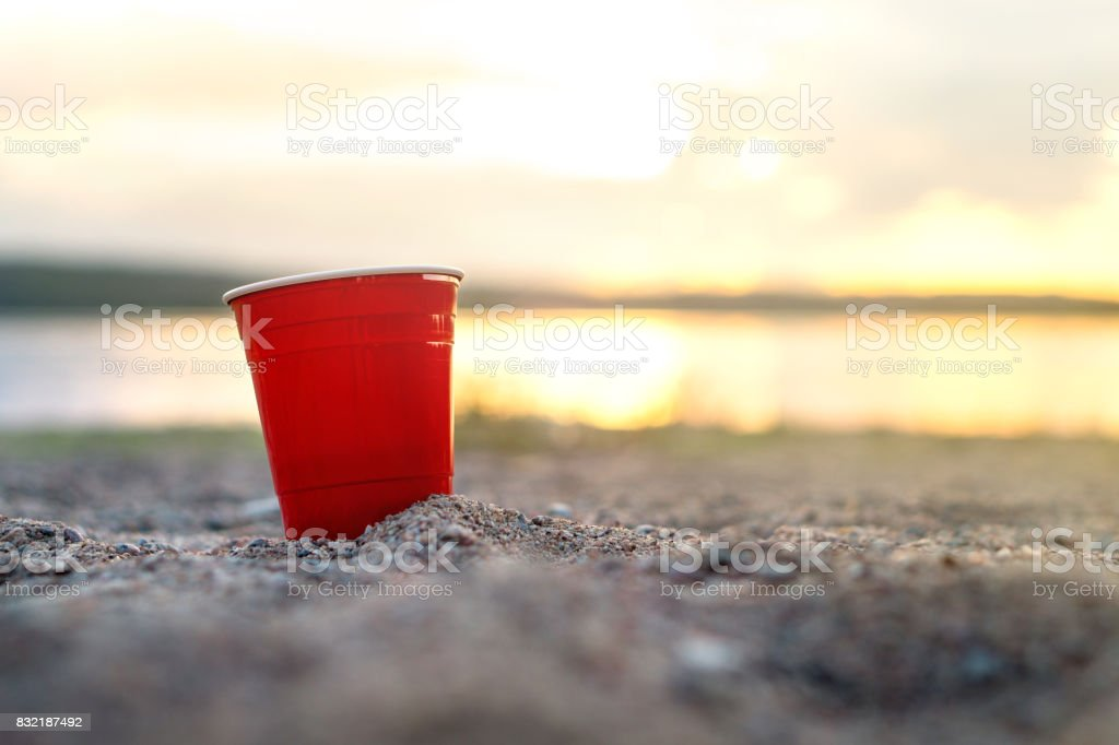 Red party cup in sand at sunset. Summer beach party concept with copy space. stock photo