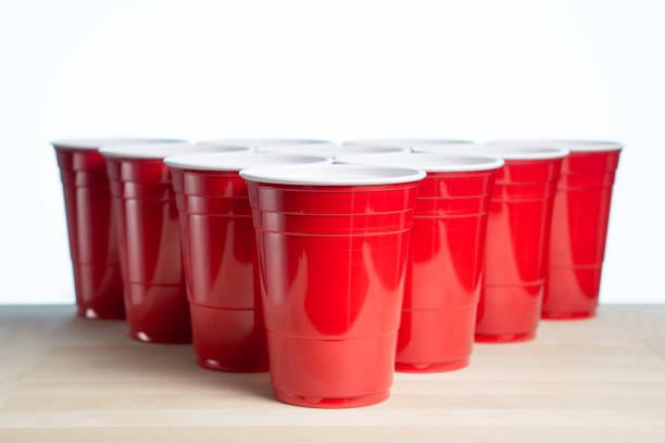 rode partij bekers op houten tafel voor bier pong toernooi op wit wordt geïsoleerd. college alcohol containers met presentexemplaar lege lege ruimte voor tekst. gebeurtenis marketing en promotie achtergrond sjabloon. - beirut stockfoto's en -beelden