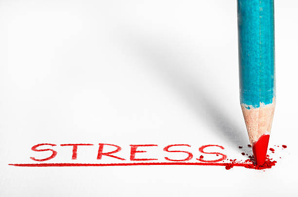 Red pastel pencil writing the word Stressed out stock photo