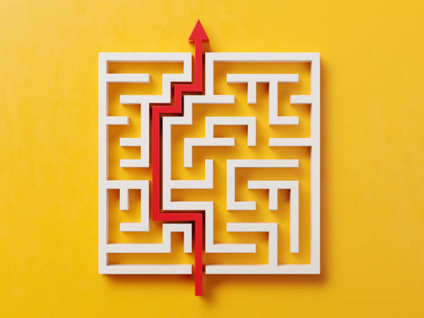 red path across a white maze on yellow background - maze stock photos and pictures