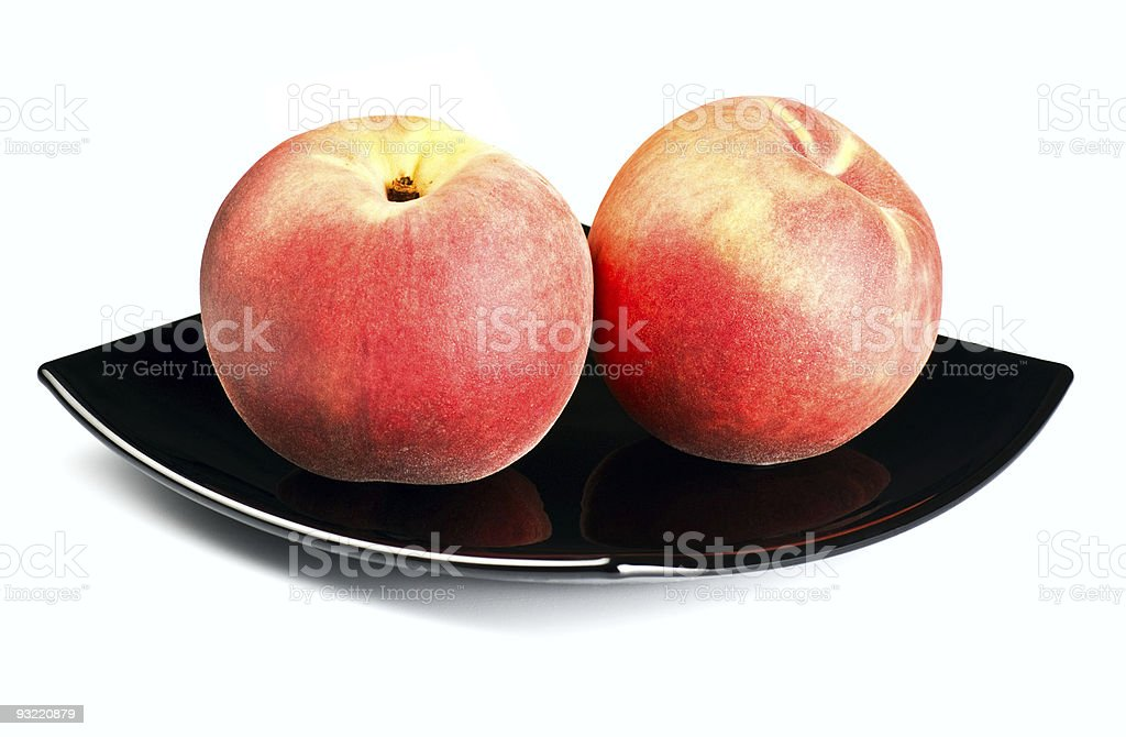 red peaches on black dish stock photo