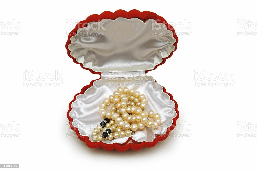Red peal-shaped box with pearl beads isolated on white royalty-free stock photo