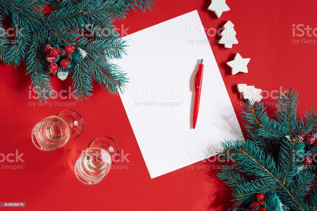 Caneta vermelha e o bloco de notas na mesa vermelha decorada com um ramo de abeto. O plano de fundo para o texto - foto de acervo