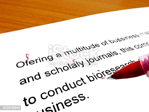 istock Red pen correcting proofread english text on wooden table 535848945