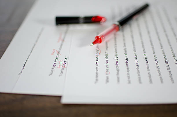 Red pen editing a manuscript stock photo