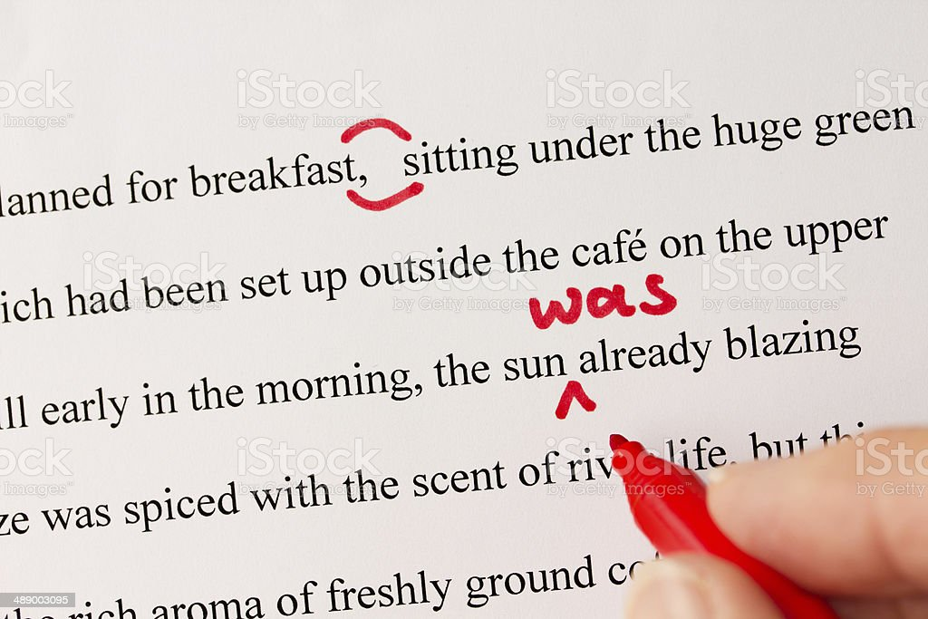 Red Pen Proofreading a Manuscript by Laptop stock photo
