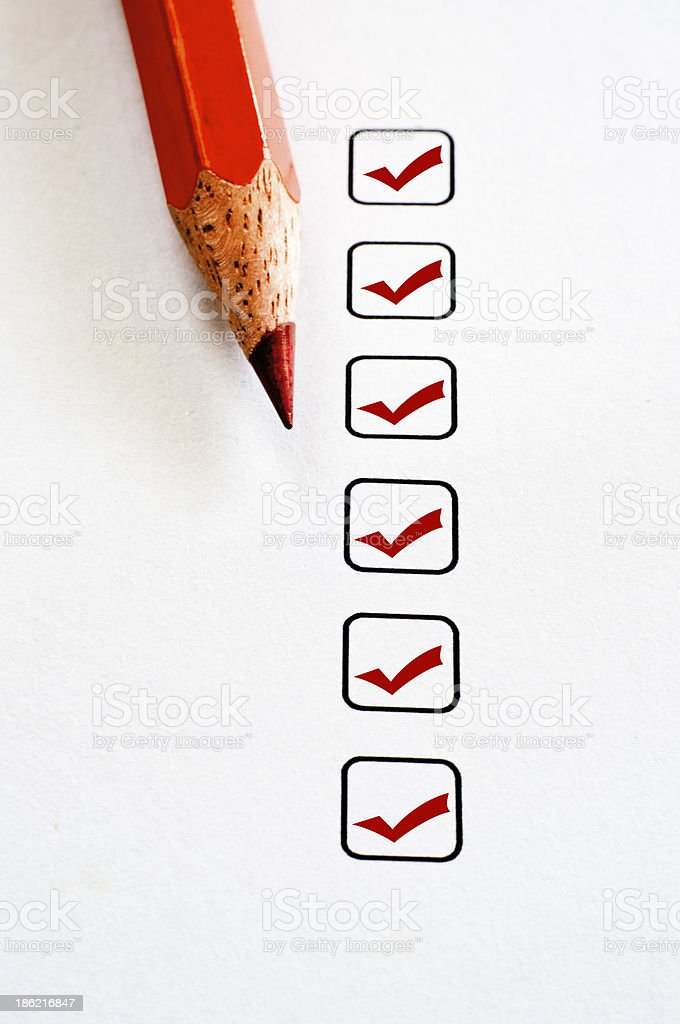 Red pencil crayon next to tick boxes stock photo