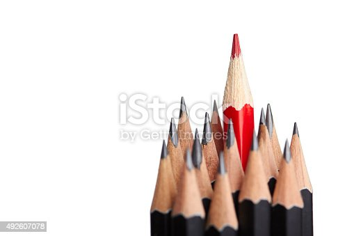 Red pencil standing out from crowd of plenty identical black fellows on white backgroung. Leadership, uniqueness, independence, initiative, strategy, dissent, think different, business success concept