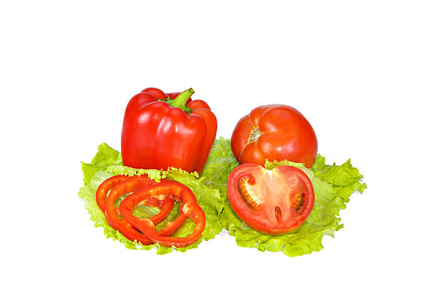 Red pepper and tomato with slices on lettuce leaves.
