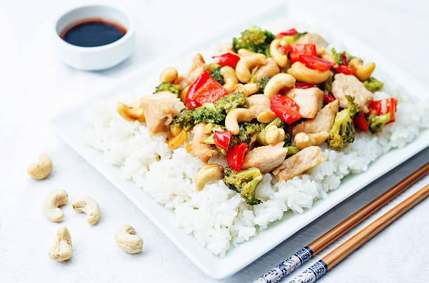 rote paprika brokkoli cashew-hühnergeschnetzeltes mit reis - huhn brokkoli auflauf stock-fotos und bilder