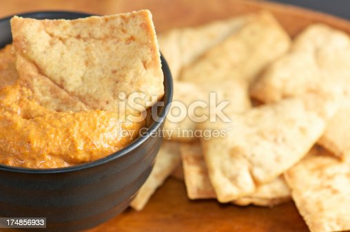 Roasted red pepper dip or muhammara in black bowl with pita chips