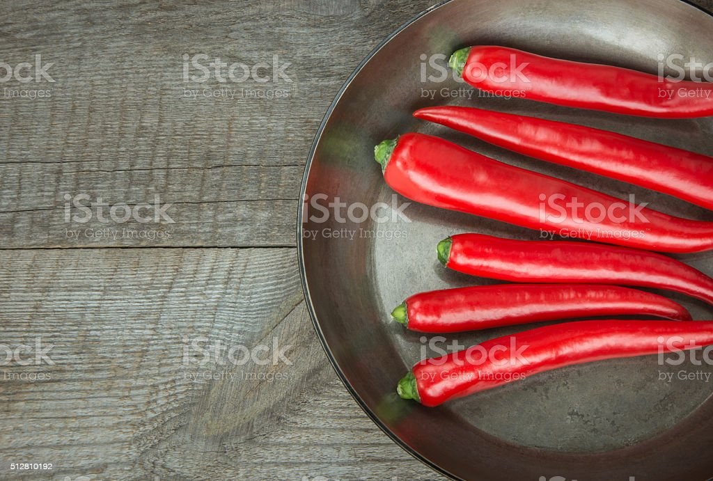 Red Peppers and pan on wooden board. Top view. stock photo