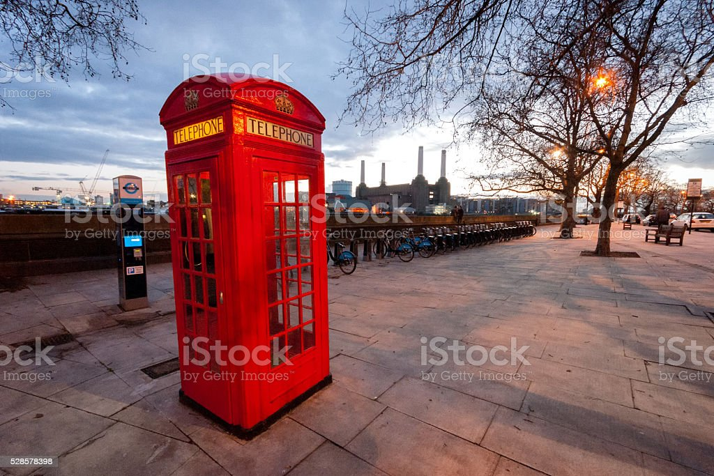 Red phone booth with Battersea power station in the background stock photo