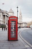 London, UK - April 13, 2019: Front view of a red phone box on Pall Mall East, National Gallery on the background. Red phone boxes can be found in current or former British colonies around the world.