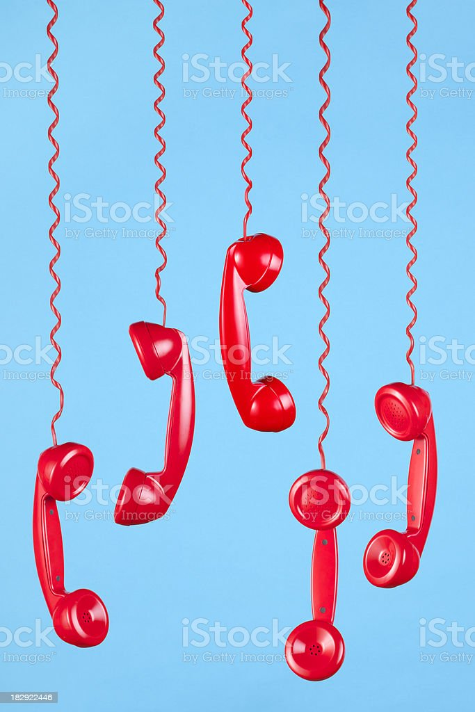 Red Phones Hanging on a Blue Background stock photo